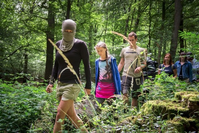 image showing several activists, one of them Greta, walking through the forest. One of them is masked.